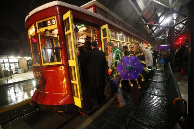 """Costumed members of the """"Societe des Champs Elysee"""" board the Rampart-St. Claude street car line, which just opened last fall, to commemorate the official start of Mardi Gras season, in New Orleans, Friday, January 6, 2017. (Photo by Gerald Herbert/AP Photo)"""