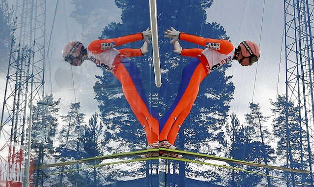 Stefan Kraft of Austria is mirrored during his jump in a training session of the men's normal hill individual HS100 ski jumping at the Nordic World Ski Championships in Falun February 19, 2015. (Photo by Kai Pfaffenbach/Reuters)