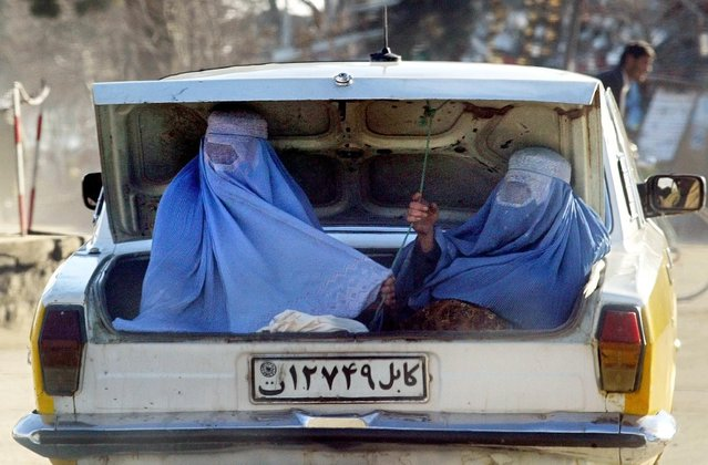 Veiled Afghan women ride in the trunk of a car in Charikar, north of Kabul, Afghanistan on February 18, 2003. (Photo by Reuters/Stringer)