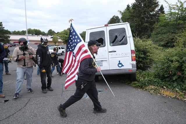 A man reacts after anti-fascist protesters drove towards members of the far-right group Proud Boys as they rally in an abandoned parking lot on Sunday, August 22, 2021, in Portland, Ore. (Photo by Alex Milan Tracy/AP Photo)