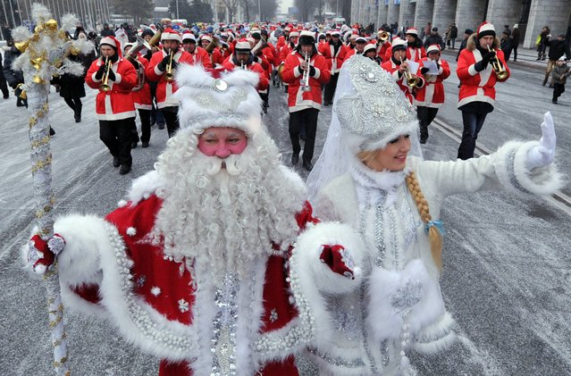 Actors dressed as the Russian Ded Moroz (Grandfather Frost) (L) and his companion Snegurochka (Snow Maiden) (R) take part a New Year parade in the Kyrgyzstan's capital Bishkek on December 31, 2013. New Year, which was the biggest informal holiday of the year in the former Soviet Union, is also very popular in predominantly Muslim Central Asian nation of Kyrgyzstan. (Photo by Vyacheslav Oseledko/AFP Photo)