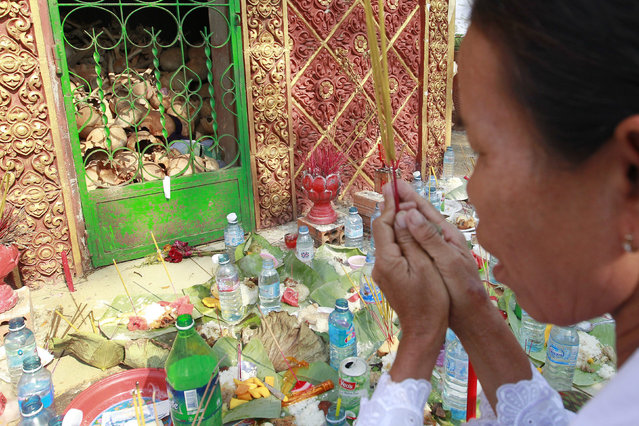 A Cambodian woman prays for her relatives who died during the Khmer Rouge regime during a ceremony at a victim memorial stupa in Kampot province, Cambodia, 15 April 2015. Cambodian relatives of the Khmer Rouge victims hold the ceremony to pray for the victims who died during the cruel rule of the Khmer Rouge regime from 1975-1979. (Photo by Mak Remissa/EPA)