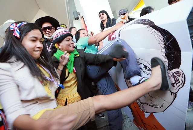 Thai anti-government protesters kick and hit at the drawing of Tharit Pengdit, chief of the Department of Special Investigation (DSI), after storming into his office during a rally in Bangkok, Thailand Monday, December 23, 2013. (Photo by Wason Wanichakorn/AP Photo)