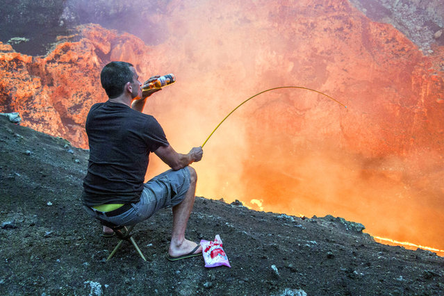 A daredevil has taken roasting on an open fire to a whole new level – heating up his marshmallows over a volcano. Brave Bradley Ambrose filmed colleague Simon Turner as the two descended towards a lava lake inside Marcum Crater in Ambrym, Vanuatu. Simon, from Christchurch, New Zealand, wanted to make the trip more memorable so brought a bottle of beer and some marshmallows to roast. He used a spare tent peg which he took with him on the 400m deep descent towards the lava lake and temperatures of more than 2000F. A seasoned volcano expert, Bradley has made the descent towards the lava lake 12 times in the past – almost three miles of rappelling. (Photo by Bradley Ambrose/Caters News Agency)