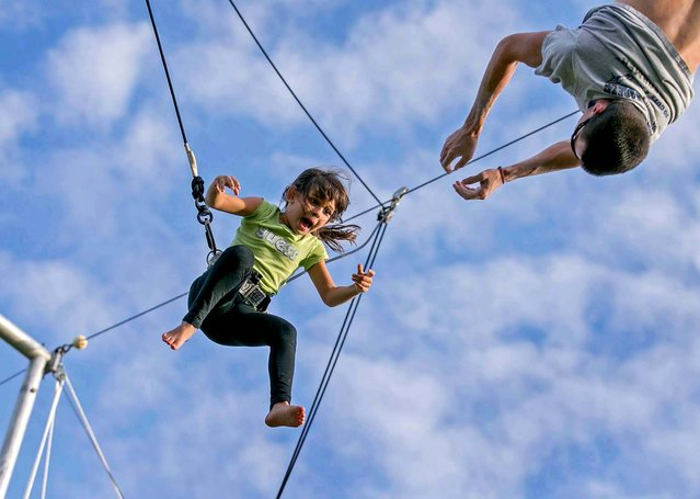 Jordan Lewis, 6, of Loxahatchee, is released by Aerial Trapeze Academy catcher Thomas Cave as she practices at the first Winter Break Sports & Circus Arts Day Camp at Village Park in Wellington, on January 3, 2013. (Photo by Allen Eyestone/The Palm Beach Post)