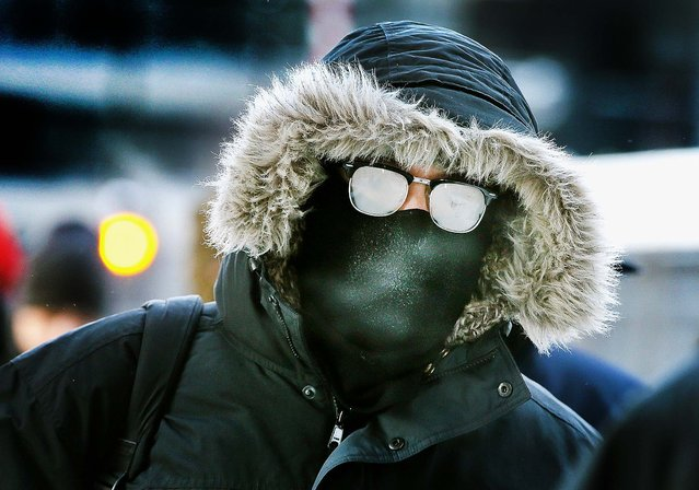 Commuters make a sub-zero trek, causing glasses to fog up, to offices in the Loop in Chicago. Temperatures in the city dipped to -16 degree Fahrenheit Monday morning on the heals of a polar vortex that has swept into the Midwest bringing with it dangerously cold temperatures not seen in the area in about 20 years.  (Photo by Scott Olson/Getty Images)