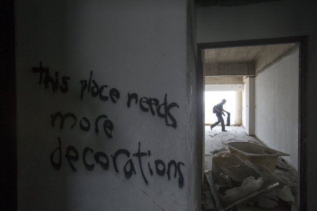A visitor walks inside an abandoned building in Bangkok April 19, 2015. (Photo by Athit Perawongmetha/Reuters)