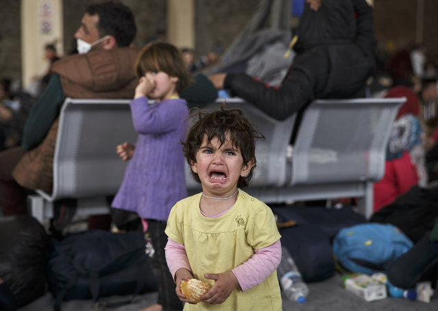 A girl cries after becoming temporarily separated from her family after more than 1.000 people were ferried in to an already overcrowded shelter area at the Athens' port of Piraeus, Tuesday, March 1, 2016. (Photo by Vadim Ghirda/AP Photo)