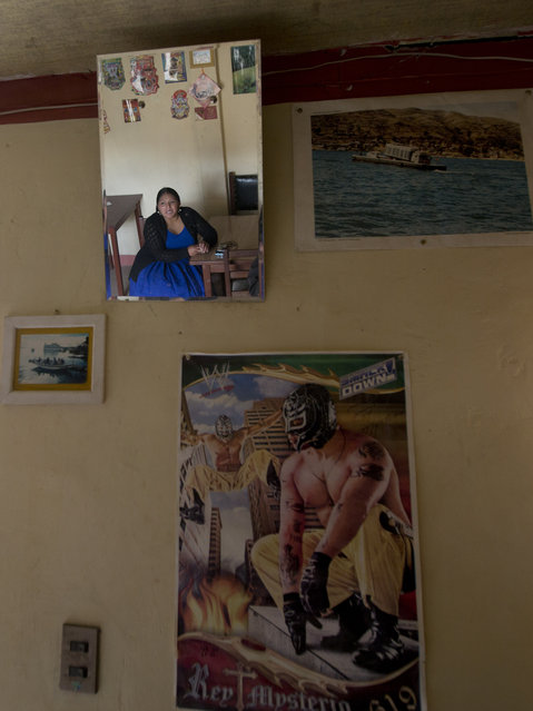 Veteran cholita wrestler Reyna Torrez is reflected in a mirror next to a poster of Mexican professional wrestler Rey Mysterio during an interview at her home in El Alto, Bolivia, Monday, February 18, 2019. Torrez, who competes in the ring as Leydi Huanca, is among the most famous cholita wrestlers who has entertained spectators for a dozen years. (Photo by Juan Karita/AP Photo)