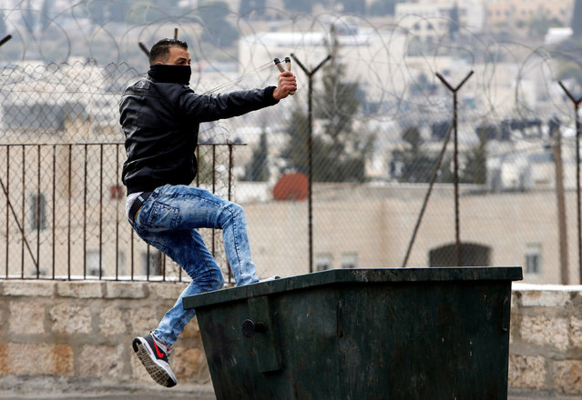 A Palestinian protester uses a slingshot to hurl stones towards Israeli troops during clashes in the West Bank city of Bethlehem January 26, 2017. (Photo by Mussa Qawasma/Reuters)