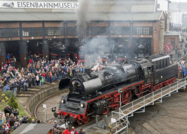 Visitors admire a  steam locomotive during the Dresden Steam Locomotive Festival, the biggest steam engine spectacle in Germany, in the maintenance depot of the railway museum  in Dresden, eastern Germany, Saturday, April 18, 2015. (Photo by Jens Meyer/AP Photo)