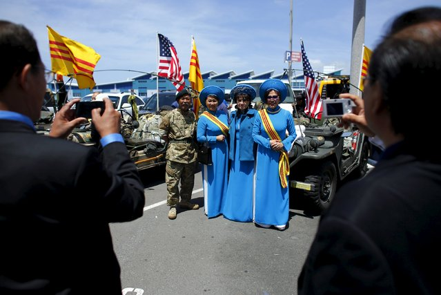 Visiting members of the Vietnamese community pose for a picture in front of antique military jeeps as they arrive to attend a ceremony on the flight deck of the USS Midway commemorating the 40th Anniversary of Operation Frequent Wind and the fall of Saigon in San Diego, California, United States  April 26, 2015. (Photo by Mike Blake/Reuters)