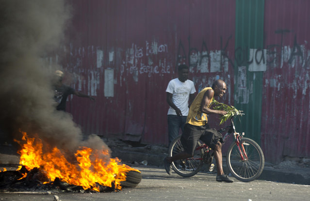 Demonstrators run away during a protest to demand the resignation of President Jovenel Moise and demanding to know how Petro Caribe funds have been used by the current and past administrations, in Port-au-Prince, Haiti, Saturday, February 9, 2019. (Photo by Dieu Nalio Chery/AP Photo)