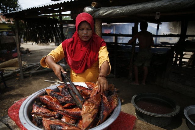 A vendor grills fish during processing on Maitara island before selling it at the local Tidore market in North Maluku province, Indonesia, March 11, 2016. (Photo by Reuters/Beawiharta)