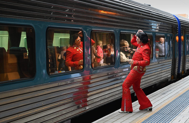 An Elvis fan uses the train window as a mirror at Central station before boarding a train to The Parkes Elvis Festival, in Sydney on January 10, 2019. The Parkes Elvis Festival is an annual event celebrating the music and life of Elvis Presley in the New South Wales town of Parkes. (Photo by Peter Parks/AFP Photo)