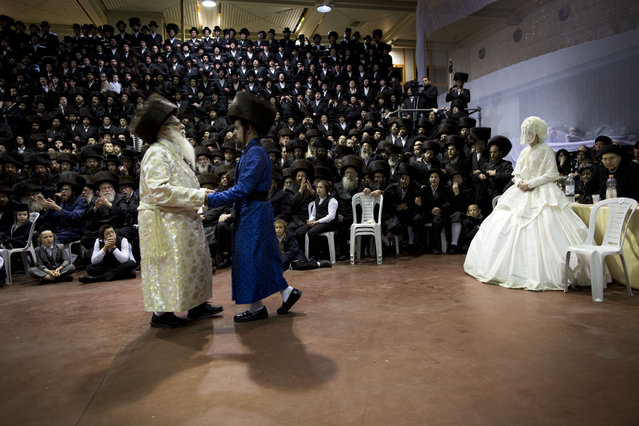 An ultra-Orthodox Jewish bride enters to the men's section of the wedding, to fulfill the Mitzvah tantz, in which family members and honored rabbis are invited to dance in front of the bride, often holding a gartel, and then dancing with the groom, during her wedding to the grandson of the Rabbi of the Tzanz Hasidic dynasty community, in Netanya, Israel, Wednesday, March 16, 2016. (Photo by Oded Balilty/AP Photo)