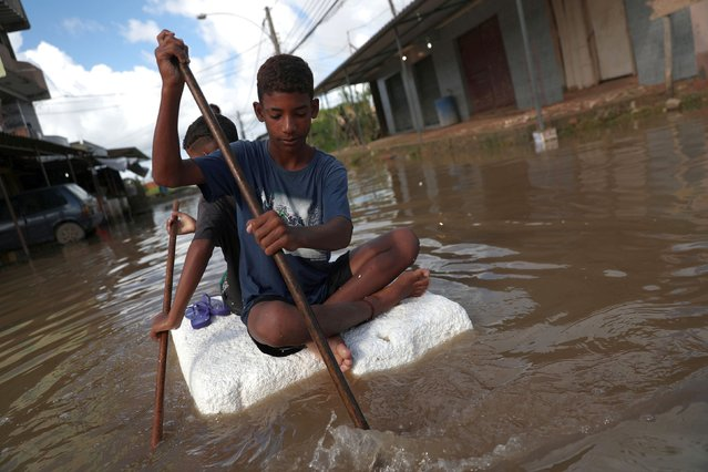 Kids row on a styrofoam block through a flooded street during heavy rains in the Guaratiba neighborhood in Rio de Janeiro, Brazil April 10, 2019. (Photo by Ricardo Moraes/Reuters)