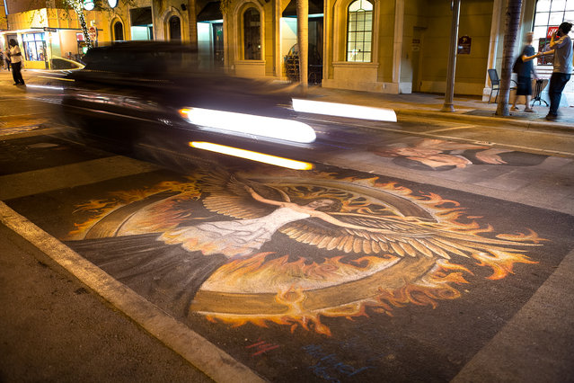 Cars drive over the remnants of artwork from, Sunday night. (Photo by Madeline Gray/The Palm Beach Post)