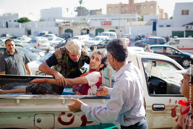 A Libyan Rebel soldier unloads a wounded fellow fighter for medical attention to the Tripoli Central Hospital