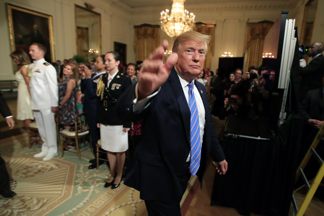 President Donald Trump waves as he leaves the East Room during a celebration of military mothers with first lady Melania Trump at the White House in Washington, Friday, May 10, 2019. (Photo by Manuel Balce Ceneta/AP Photo)