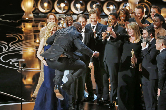 """Director and producer Steve McQueen jumps after accepting the Oscar for best picture for his work in """"12 Years a Slave"""" at the 86th Academy Awards in Hollywood, California March 2, 2014. (Photo by Lucy Nicholson/Reuters)"""