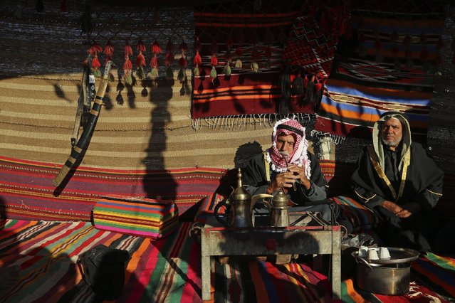 Mahmoud el-Deeb, 77, left, plays music as he sits with his neighbor Ali Qarra, 75, right, while sitting at a traditional tent as they mark the Nakba Day in Zaneh, neighborhood east of Khan Younis, in the southern Gaza Strip, Friday, May 15, 2015. Palestinians marked the Nakba Day, or the Day of the Catastrophe, when hundreds of thousands of Palestinians were expelled from their towns during the first Israeli-Arab war in 1948. (Photo by Adel Hana/AP Photo)