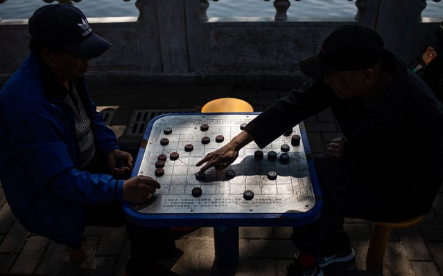Men play Chinese chess near the Houhai lake in Beijing, China, 10 April 2019. (Photo by Roman Pilipey/EPA/EFE)
