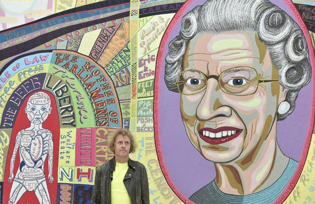 "British artist Grayson Perry poses in front of his tapestry, ""Comfort Blanket"" at the launch of his show ""Provincial Punk"" at the Turnery Contemporary in Margate in south east England, May 22 , 2015. Over fifty of Perry's artworks, consisting of ceramics, paintings, sketch books and large tapestries are on show until September 13. (Photo by Toby Melville/Reuters)"