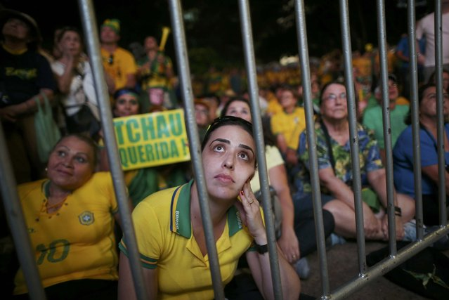 Brazilians in favor of the impeachment of President Dilma Rousseff react while watching the televised voting of the Lower House of Congress over her impeachment in Brasilia, Brazil April 17, 2016. (Photo by Adriano Machado/Reuters)