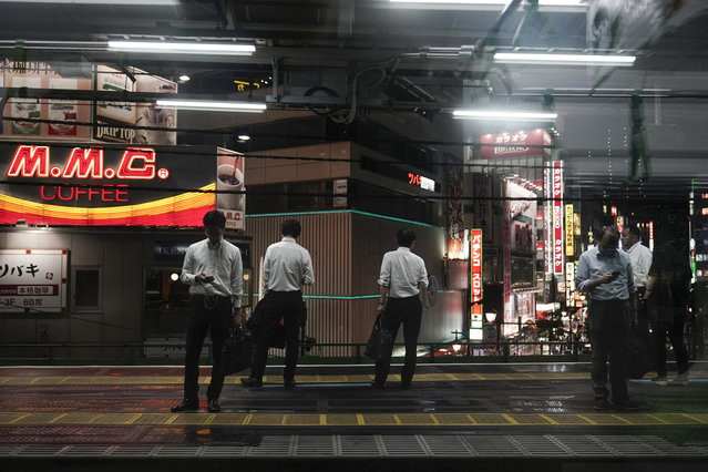 In this Friday, May 24, 2019, photo, commuters waiting for a train are seen through the window of a Yamanote Line train at Shimbashi Station in Tokyo. Running above ground, views from wide windows on the train range from high-rises to local shopping arcade as the train covers different parts of the city. The line, according to company statistics, moves roughly 3 to 4 million people daily, more than the entire population of Jamaica. (Photo by Jae C. Hong/AP Photo)