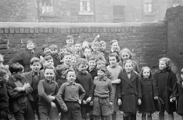 Boys and girls pose for the camera in the Gorbals, a slum district of Glasgow, 1948. (Photo by Bert Hardy/Picture Post/Hulton Archive/Getty Images)