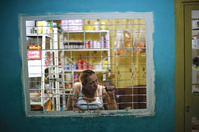 """A woman looks out of a window at her shop in a corridor inside the """"Tower of David"""" skyscraper in Caracas. (Photo by Jorge Silva/Reuters)"""