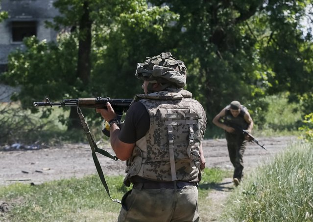 """Members of the Ukrainian armed forces patrol an area in the town of Maryinka, eastern Ukraine, June 5, 2015. Ukraine's president told his military on Thursday to prepare for a possible """"full-scale invasion"""" by Russia all along their joint border, a day after the worst fighting with Russian-backed separatists in months.  REUTERS/Gleb Garanich"""