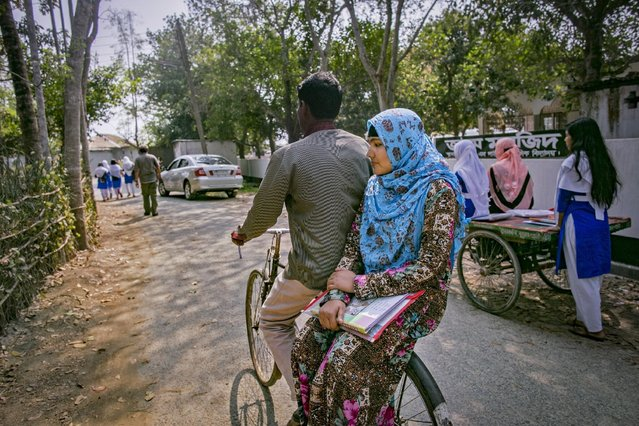 Rani rides home with her father on the back of his bicycle on March 6, 2017 in Khulna division, Bangladesh. Rani, who is now 16, was under pressure to marry a boy when she was 14-years-old despite the reluctance of Rani and her father, Abdul. (Photo by Allison Joyce/Getty Images)