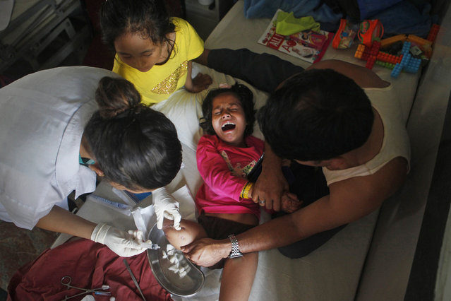In this July 24, 2015 photo, Khendo Tamang, 8, in yellow, stands by the bedside of her best friend Nirmala Pariyar, also 8, as she cries in pain during treatment on her amputated right leg in the Bir Trauma Center in Kathmandu, Nepal. Losing a leg each in the massive Nepal earthquake in 2015, they were both taken to Bir Hospital and Kathmandu's main trauma ward where they spent the next three months with surgeries and physical therapy with their new prostheses. During this time the girls' friendship grew and have become inseparable. (Photo by Niranjan Shrestha/AP Photo)
