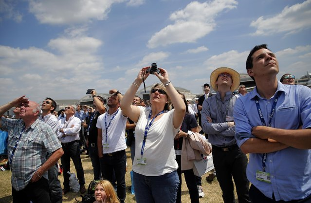 Visitors watch a Rafale jet fighter during a demonstration flight of the Paris Air Show, at Le Bourget airport, north of Paris, Wednesday, June 17, 2015. Some 300,000 aviation professionals and spectators are expected at this week's Paris Air Show, coming from around the world to make business deals and see dramatic displays of aeronautic prowess and the latest air and space technology. (AP Photo/Christophe Ena)
