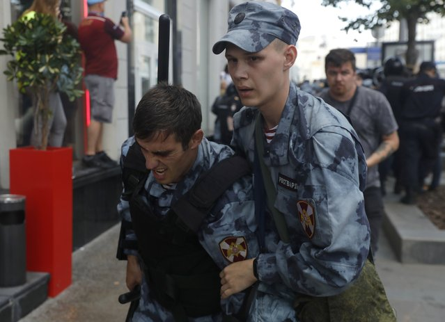 Police officer helps his comrade after he was injured in clashes with protesters during an unsanctioned rally in the center of Moscow, Russia, Saturday, July 27, 2019. (Photo by Pavel Golovkin/AP Photo)