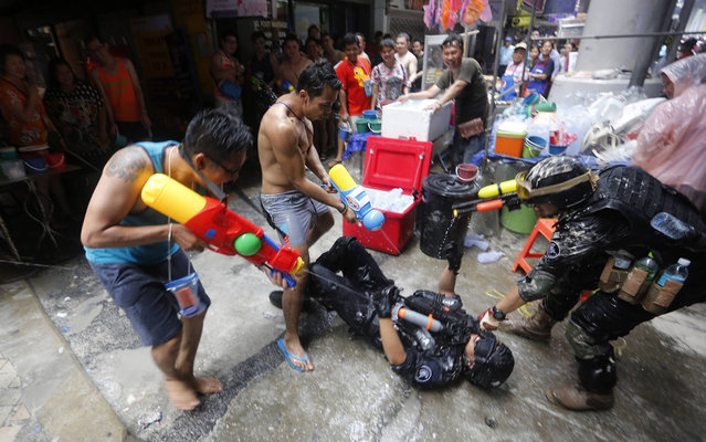 Revellers take part in a water fight during Songkran Festival celebrations on Silom Road in Bangkok April 14, 2014. The Songkran festival, also known as the water festival, marks the start of Thailand's traditional New Year and is believed to wash away bad luck. (Photo by Darren Whiteside/Reuters)