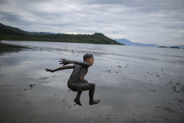 "A boy jumps into a pool of mud during the traditional ""Bloco da Lama"" or ""Mud Street"" carnival party, in Paraty, Brazil, Saturday, February 25, 2017. Legend has it the ""bloco"" was born in 1986 after local teens hiking in a nearby mangrove forest smeared themselves with mud to discourage mosquitoes and then wandered through Paraty. The party grew year after year, but revelers eventually were banned from parading in the colonial downtown after shopkeepers complained pristine white walls were stained with the hard-to-remove mud. (Photo by Mauro Pimentel/AP Photo)"