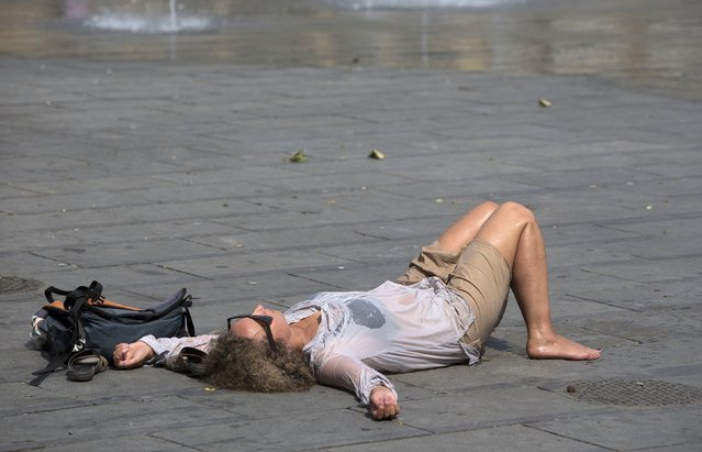 A woman rests next to a fountain on a hot summer day in central Brussels, Belgium, July 2, 2015. The United Nations warned on Wednesday of the dangers posed by hot weather, especially to children and the elderly, as much of Europe sweltered in a heatwave whose intensity it blamed on climate change. (Photo by Yves Herman/Reuters)