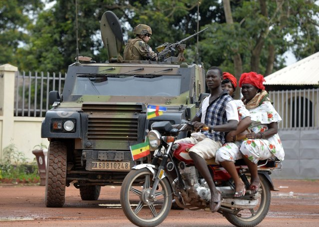 """People ride a motorbike as French soldiers part of the Sangaris operation stand guard in Bangui on April 21, 2014. The United Nations has evacuated almost 100 Muslims from the capital of the crisis-torn Central African Republic to """"save their lives"""", according to officials on April 22, 2014. The former French colony, one of the poorest countries in the world, plunged into a crisis after a coup by the mostly Muslim Seleka rebels in March last year. (Photo by Miguel Medina/AFP Photo)"""