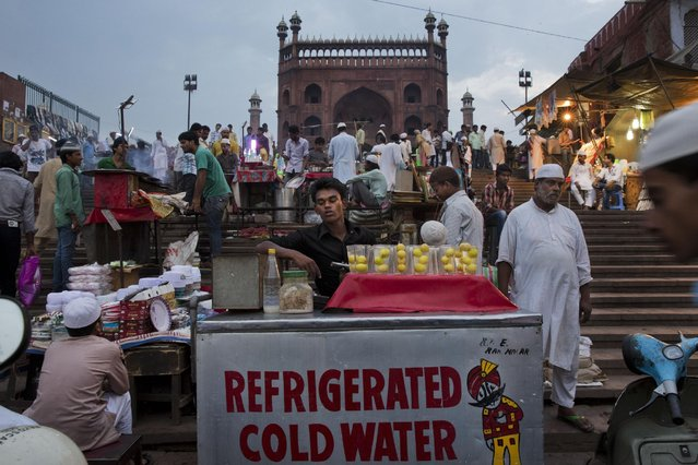 Indian street vendors wait for customers outside the Jama Masjid mosque during the holy month of Ramadan, in New Delhi, India, Friday, July 3, 2015. (Photo by Bernat Armangue/AP Photo)