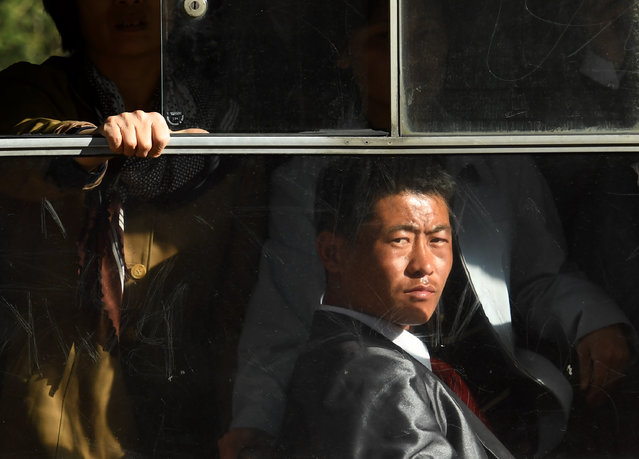 Workers ride the trolley in downtotwn Pyongyang, North Korea on May 4, 2016. (Photo by Linda Davidson/The Washington Post)