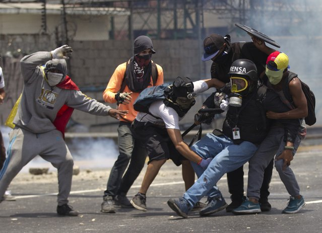 Demonstrators help a journalist who was injured in a leg while covering clashes between demonstrators and the  Bolivarian National Guard during a protest in Caracas, Venezuela, Monday, April 10, 2017. (Photo by Ariana Cubillos/AP Photo)