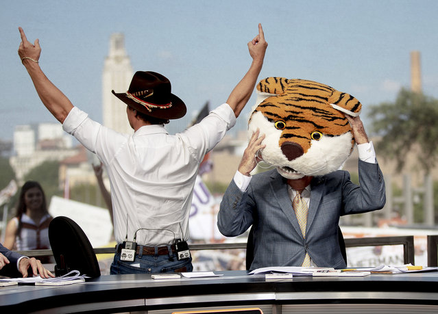 """Matthew McConaughey holds up the """"Hook Em Horns"""" sign while College GameDay host Lee Corso puts on the LSU mascot head during ESPN's College GameDay broadcast on Saturday, September 7, 2019, in Austin, Texas. (Photo by Nick Wagner/Austin American-Statesman via AP Photo)"""
