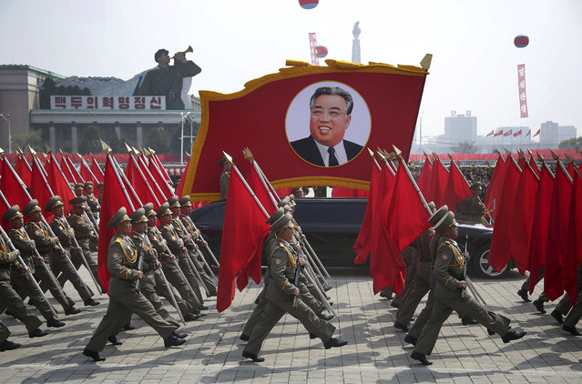 North Korean soldiers carry flags and a photo of late leader Kim Il Sung as they march across Kim Il Sung Square during a military parade on Saturday, April 15, 2017, in Pyongyang, North Korea to celebrate the 105th birth anniversary of Kim Il Sung, the country's late founder and grandfather of current ruler Kim Jong Un. (Photo by Wong Maye-E/AP Photo)