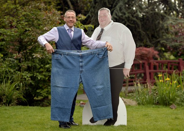 Stuart Eggleshaw from Kirkby-in-Ashfield poses with his old trousers and a photograph of him before the weight loss, as he is announced as Slimming World Greatest Loser 2014 after losing 22st 9lbs at Kensington Roof Gardens, London, on May 7, 2014. (Photo by Anthony Devlin/PA Wire)