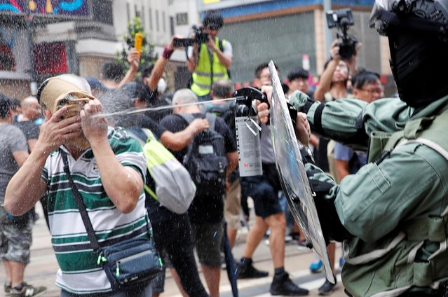 A riot police officer pepper sprays an anti-government protester during a demonstration at Causeway Bay district in Hong Kong, China on September 29, 2019. (Photo by Tyrone Siu/Reuters)