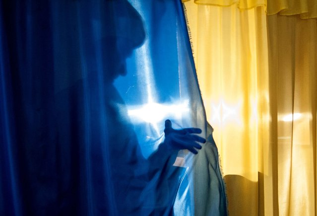 A woman casts a shadow on leaving a booth to cast her ballot at a polling station in Luhansk, Ukraine, on May 11, 2014. Residents of two restive regions in eastern Ukraine cast ballots Sunday in referendums which seek approval for declaring sovereign people's republics in the Donetsk and Luhansk regions. (Photo by Evgeniy Maloletka/Associated Press)