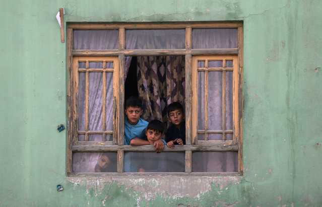 Afghan children look out from a broken window at the site of a blast in Kabul, Afghanistan on September 3, 2019. (Photo by Omar Sobhani/Reuters)